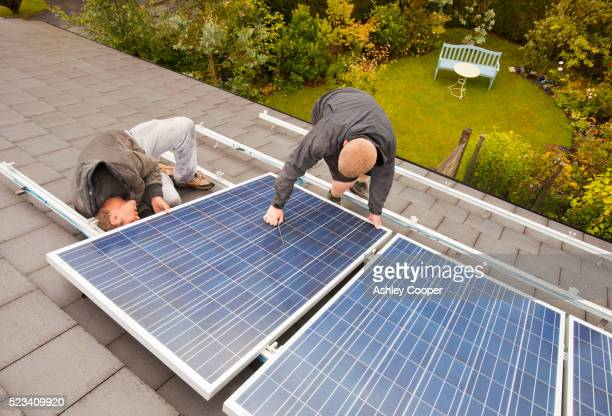 technicians fitting solar photo voltaic panels to a house roof in ambleside, cumbria, uk. - solar panel stock pictures, royalty-free photos & images