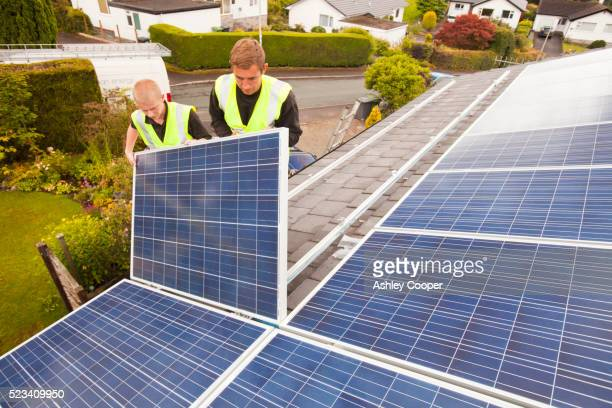 technicians fitting solar photo voltaic panels to a house roof in ambleside, cumbria, uk. - roof tile stock pictures, royalty-free photos & images