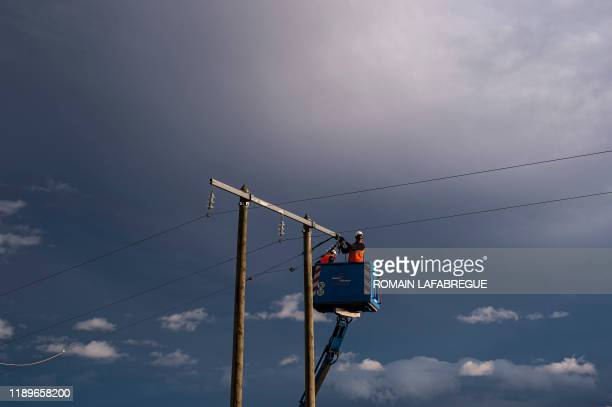 Technicians fix a power line on December 20 in Valfleury, near Saint-Etienne, central-eastern France, after high winds in the morning. - Fourteen...