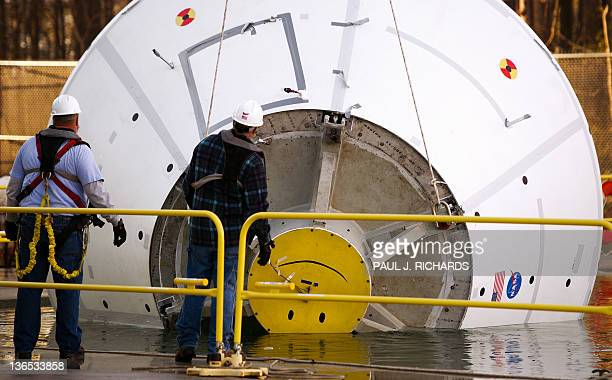 Technicians flip over the mock up of the 18000pound Orion deep space exporation vehicle that was dropped into a pool of water with an impact pitch of...