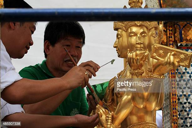 Technicians from the art department perform repairs on the facial sculpture of Lord Brahma after it was damaged by the bomb at the Erawan Shrine in...