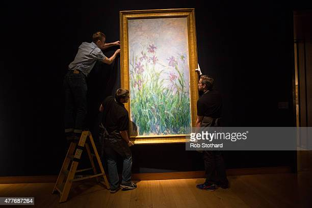 Technicians hang Claude Monet's 1914-1917 piece 'Iris mauves', estimated at between £6-9 million, at Christie's King Street auction house on June 19,...