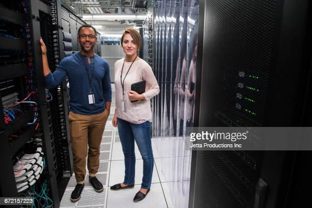 Technicians holding digital tablet in computer server room