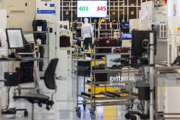 Technicians in a semiconductor cleanroom showing a production metric counter at the Interuniversity Microelectronics Centre in Leuven, Belgium, on...