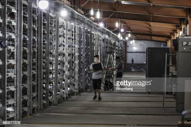 Technicians inspect bitcoin mining machines at a mining facility operated by Bitmain Technologies Ltd in Ordos Inner Mongolia China on Friday Aug 11...