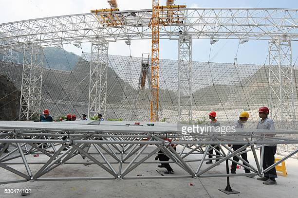 Technicians install reflectors at the construction site of a Fivehundredmeter Aperture Spherical Telescope on May 7 2016 in Pingtang County Guizhou...
