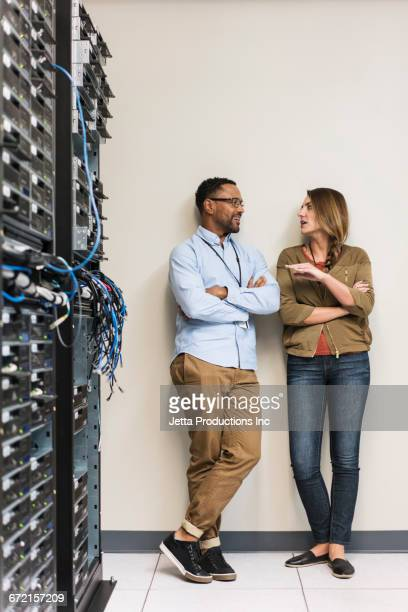Technicians leaning on wall talking in computer server room