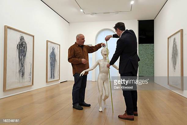 Technicians make final adjustments to a sculpture entitled 'Cri' 2013 by artist Adel Abdessemed at the David Zwirner Gallery on February 21 2013 in...