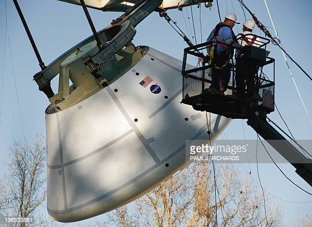 Technicians make final preparations on the 18000pound Orion deep space exporation vehicle that was soon to be dropped into a pool of water with an...