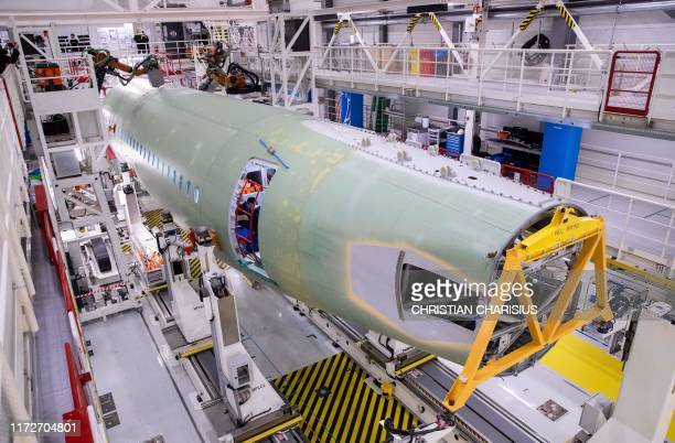 Technicians of Airbus and robots work on a fuselage segment of a plane belonging to the Airbus A320 family at the company's Finkenwerder plant in...
