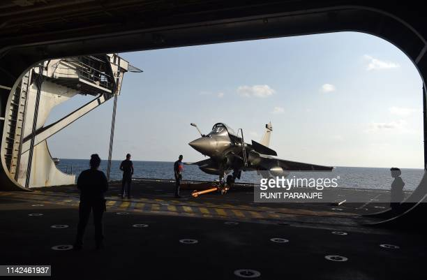 Technicians prepare to take out a French Rafale fighter jet from a hangar of the aircraft carrier Charles de Gaulle during a joint IndoFrench naval...
