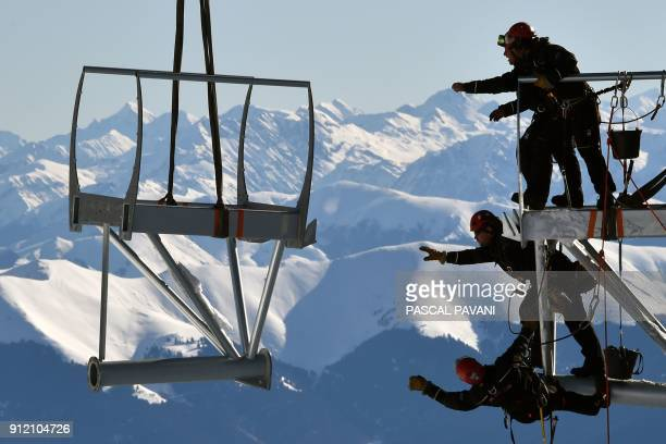 Technicians reach out to catch a piece of a metal structure during the installation of a 12meterlong platform at the top of the Pic du Midi one of...