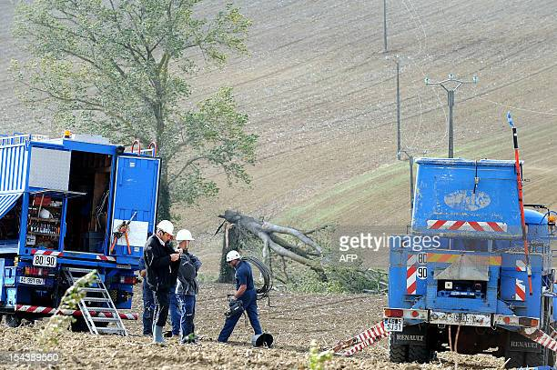 technicians repair a high voltage line damaged by a falling tree after 100 km per hour winds blew in southwestern France on October 19 2012 in Lanta...