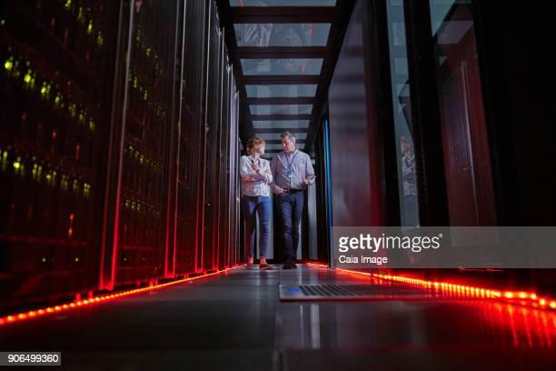 IT technicians talking and walking in dark server room