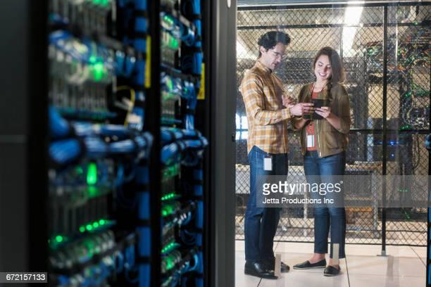 Technicians using digital tablet in computer server room