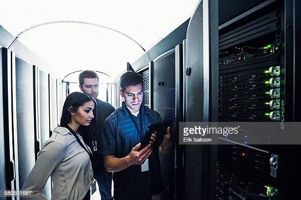 Technicians using digital tablet in server room