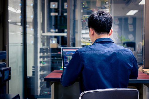 Technicians using laptop while analyzing server in server room 992574526