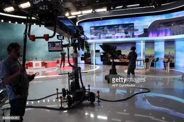 Technicians wait on the set before the broadcast news of the French TV channel France 2 on September 14 2017 in Paris / AFP PHOTO / JACQUES DEMARTHON