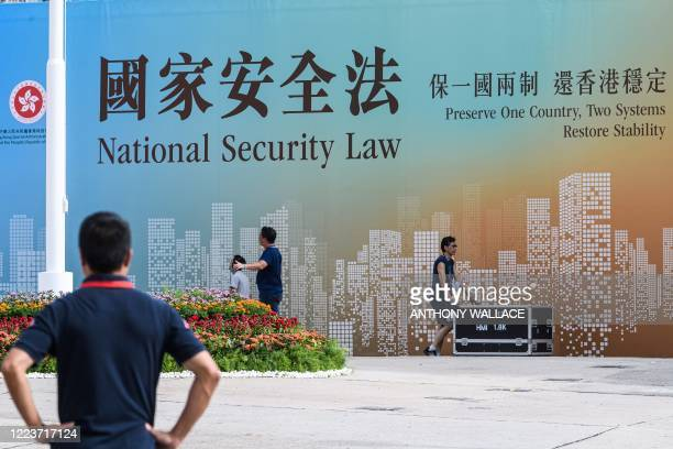 Technicians walk next to a banner supporting the new national security law at the end of a flag-raising ceremony to mark the 23rd anniversary of Hong...