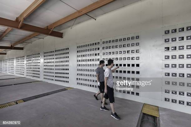 Technicians walk through a cooling chamber adjacent to a wall of bitcoin mining machines at a mining facility operated by Bitmain Technologies Ltd in...