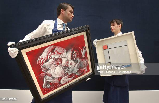 Technicians with 'Etreinte' by Picasso and hanging 'Composition with Red Yellow and Blue' by Piet Mondrian at Sotheby's in London which are to sold...