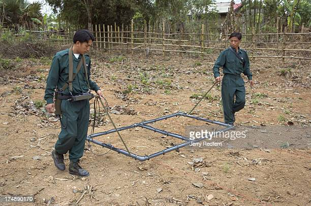 Technicians with the Mines Advisory Group use a large metal detector to sweep the grounds of the parking lot at Site 3 at the Plain of Jars. This...