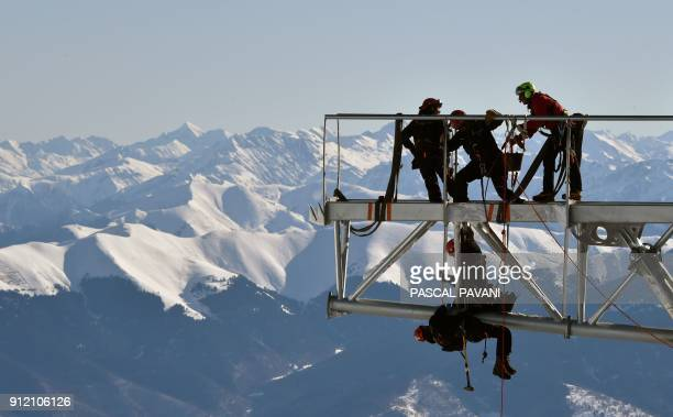 Technicians work during the installation of a 12-meter-long platform at the top of the Pic du Midi, one of France's tallest mountains, in...