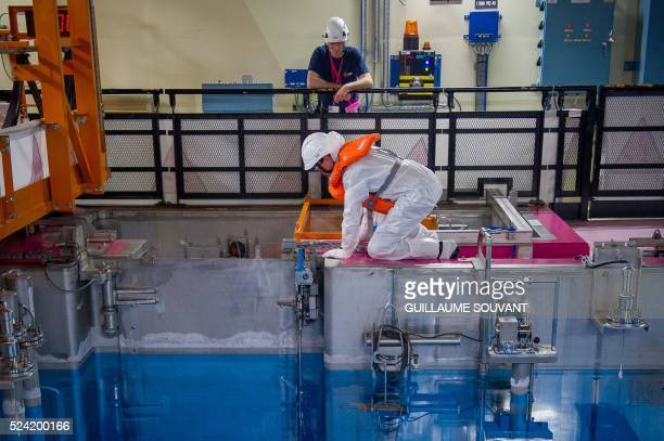 Technicians work next the cooling pool of the switched off Unit 1 reactor at the nuclear power plant of Civaux central France on April 25 during a...