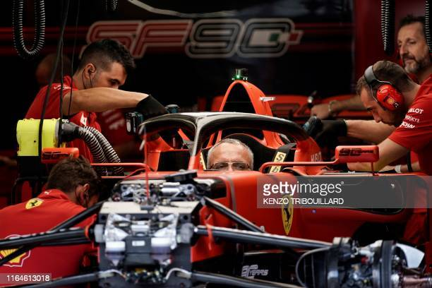 Technicians work on a car in the pits of Ferraris's F1 team during previews at the SpaFrancorchamps circuit in Spa on August 29 a few days ahead of...