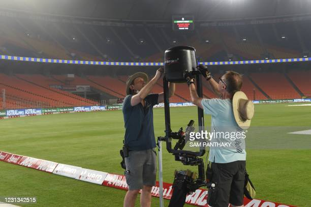 Technicians work on a spider-cam television camera at the Sardar Patel Stadium, the world's biggest cricket stadium, on the eve of the third Test...