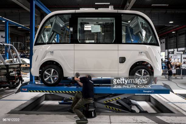 Technicians work on April 23 2018 on an autonomous driverless and electric bus shuttle at the NAVYA plant in Bron near Lyon central eastern France...