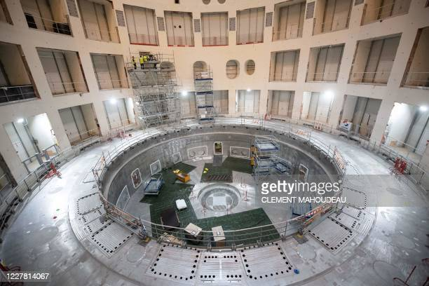 Technicians work on the bioshield inside the Tokamak Building with the base of the cryostat at its base during the launch of the assembly stage of...