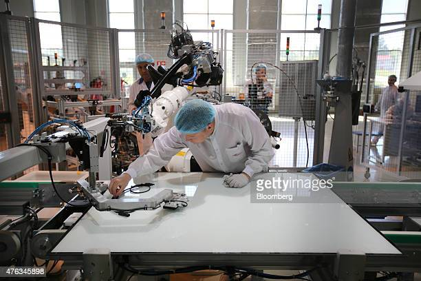 Technicians work with robotic machines during the production of solar panel modules at the Hevel Solar manufacturing plant in Novocheboksarsk Russia...