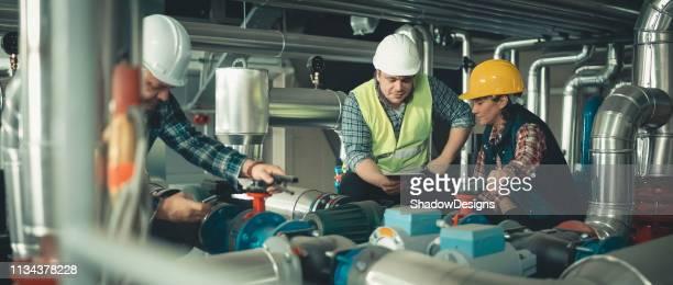 techniciens travaillant dans l'usine ou l'utilité - bouche d'aération photos et images de collection