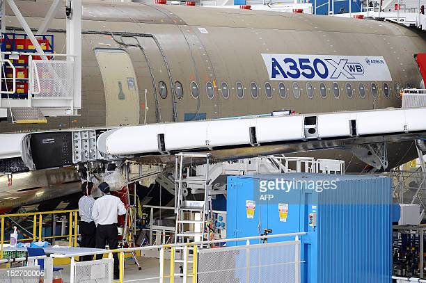 Technicians works on the Airbus longhaul plane A350 XWB assembly plant in Toulouse southern France on September 24 2012 AFP PHOTO REMY GABALDA