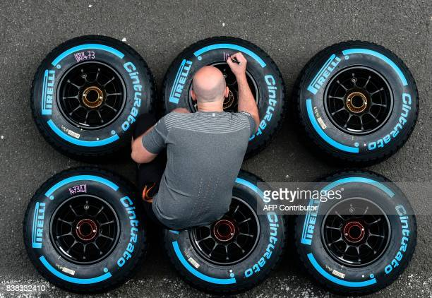 TOPSHOT A technicien of McLaren Honda Formula 1 Team writes on wheels ahead of the Formula One Grand Prix at the SpaFrancorchamps circuit in Spa on...
