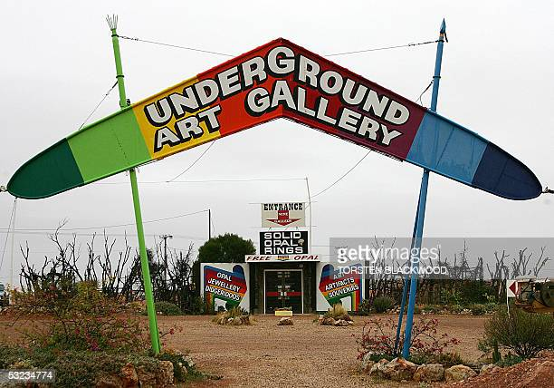 A technicoloured boomerang sign attracts tourists to an underground art gallery in the opal mining town of Coober Pedy 07 July 2005 Only 200 miners...