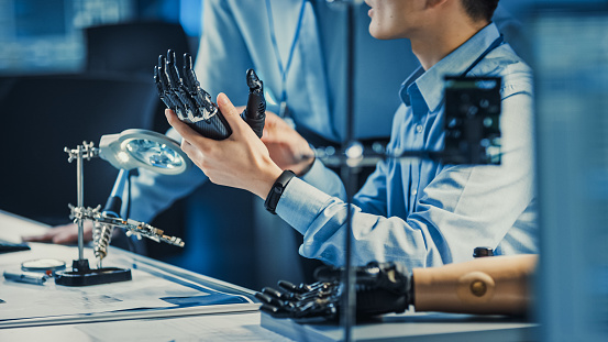 Technological Prosthetic Robot Arm is Tested by Two Professional Development Engineers in a High Tech Research Laboratory with Modern Futuristic Equipment. Compare Data on a Personal Computer. 1193074238