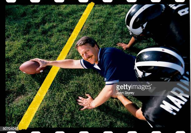 Technology officer Stan Honey on a field holding a football over a computer generated yellow line. Honey founded the company Sportvision, which...