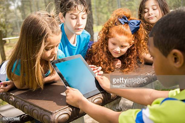 Technology: School children enjoy digital tablet outdoors at park.