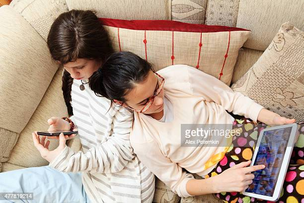 technology separating kids. two girls playing with gadgets. - alex potemkin or krakozawr stock pictures, royalty-free photos & images