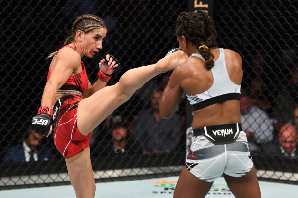 Tecia Torres kicks Angela Hill in their women's strawweight bout during the UFC 265 event at Toyota Center on August 07, 2021 in Houston, Texas.