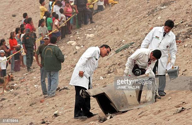 Tecnicos de la Policia Nacional inspeccionan los restos de un avion Sukhoi S22 de la Fuerza Aerea Peruana siniestrado el 17 de diciembre de 2004 en...