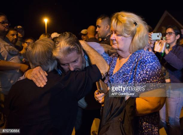 Ted and Ann Montgomery employees at the First Baptist Church are comforted by Texas Governor Greg Abbott following a candlelight vigil held across...