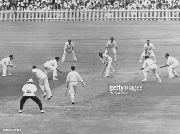Ted Dexter of England is ringed by the close in fielders of Australia as he plays a forward defensive shot to the bowling of Garth McKenzie during...