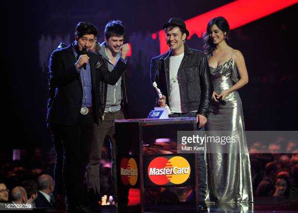 Ted Dwane Marcus Mumford Ben Lovett and WinstonMarshall of Mumford Sons receive the award for British Group from Berenice Marlohe on stage during the...
