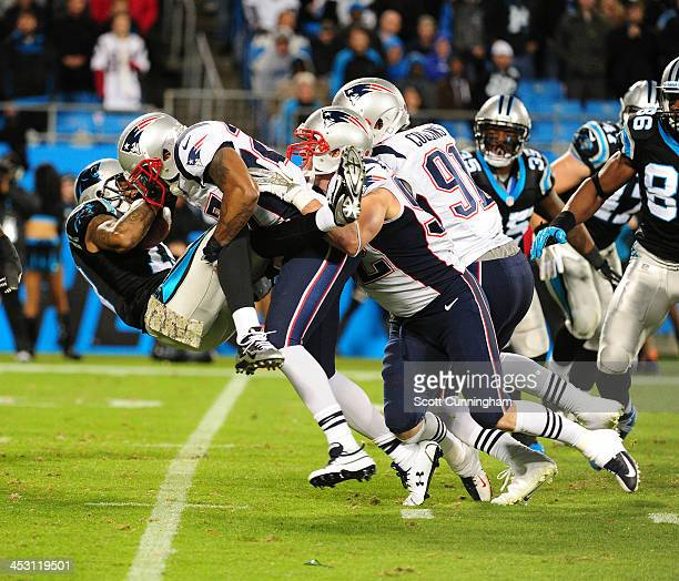 Ted Ginn Jr #19 of the Carolina Panthers is tackled by Tavon Wilson and Dane Fletcher of the New England Patriots at Bank of America Stadium on...