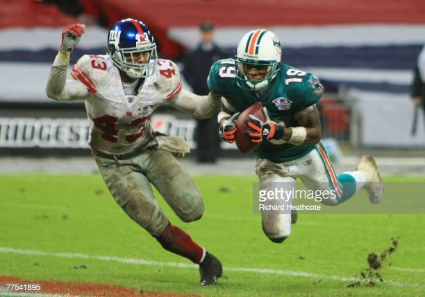 Ted Ginn Jr #19 of the Dolphins makes a touchdown reception past Michael Johnson of the Giants during the NFL Bridgestone International Series match...