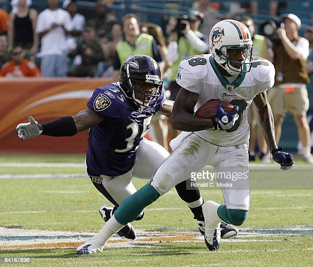 Ted Ginn Jr #19 of the Miami Dolphins carries the ball as Corey Ivy of the Baltimore Ravens chases him during the AFC Wild Card Game at Dolphin...