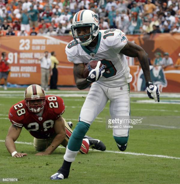 Ted Ginn Jr #19 of the Miami Dolphins runs with the ball during an NFL game against the San Francisco 49ers at Dolphin Stadium on December 14 2008 in...